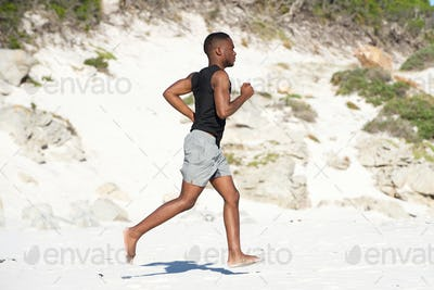 Healthy young african man running barefoot on the beach