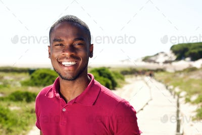 Smiling young african man standing outdoors