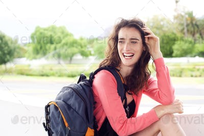 Young travel woman with backpack smiling outside
