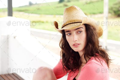 Serious young woman sitting outside in hat