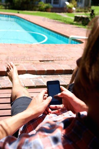 Behind young man using smart phone by pool