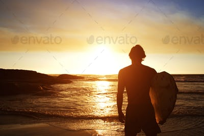 Male surfer watching the sunset at the beach