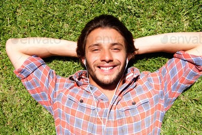 Smiling young man lying in grass listening to music