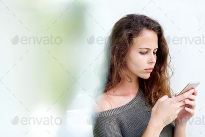 Beautiful young woman looking at mobile phone