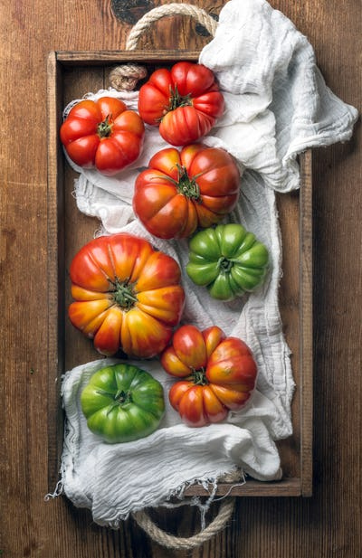 Colorful Heirloom tomatoes in rustic wooden tray