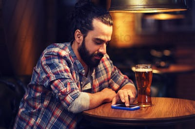 man with smartphone and beer texting at bar