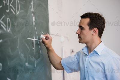 Young teacher or student draw triangle on a blackboard with formula