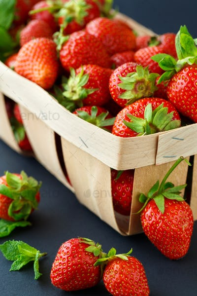 Ripe strawberries in a wooden basket on black