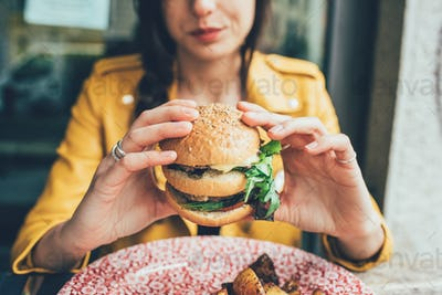 Close up on the hands of a young woman sitting holding an hamburger