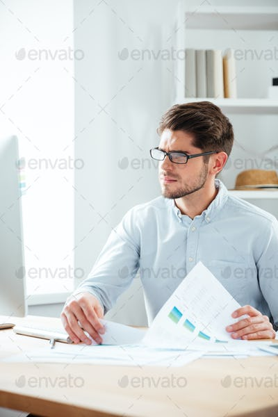 Businessman working with documents and computer in office