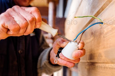 Hands of unrecognizable electrician working with screwdriver
