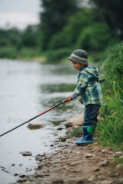 boy fishing on the coast of river