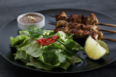 Thai chicken skewers with lime and chili, on black plate