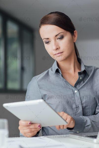 Confident businesswoman using a digital tablet