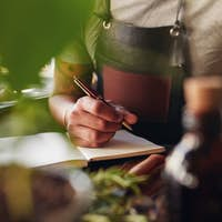 Man creating new cocktail recipe and taking notes