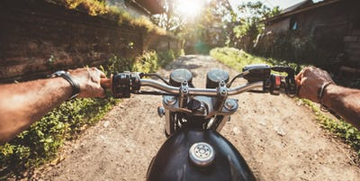 Rider driving motorcycle on a rural road
