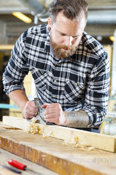 Carpenter work with planer on wood plank in workshop
