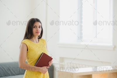 Happy pretty young female student with long blond hair clutching school books to her chest as she