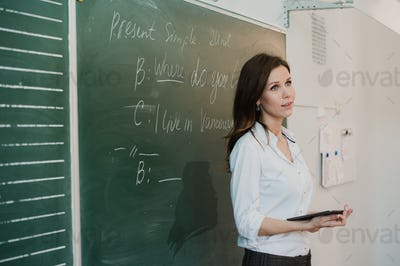 Pretty young teacher in front of a blackboard talking to class