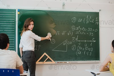 Female teacher at high school washes the chalkboard and lookng to the people in class