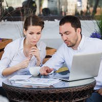 Businessman and businesswoman working outdoor at street cafe during the lunch