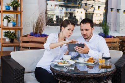 Business people looking at digital tablet in cafe during a meeting