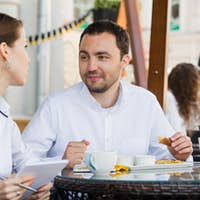 Successful manager sitting at business lunch with colleague and giving instructions to her
