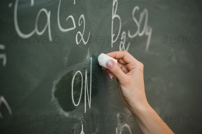 pretty young female college student writing on the chalkboard blackboard during a chemistry class