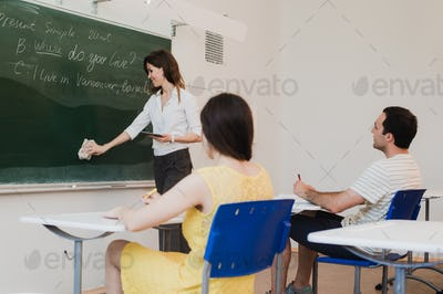 teacher stands at the blackboard and erasing washing chalkboard in front of classroom