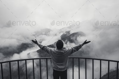Monochrome toned image young man wearing hoodie on the edge of a cliff and screams. He shows his