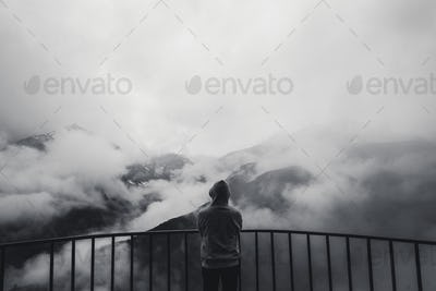 Landscape view of misty autumn mountain hills covered with fog and man silhouette in a hood