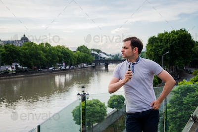 young handsome man with e-cigarette vaping and standing on the terrace near the river at european