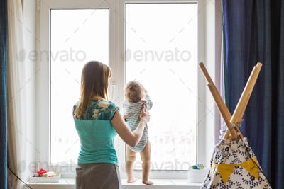 woman holding her baby girl while standing at windowsill