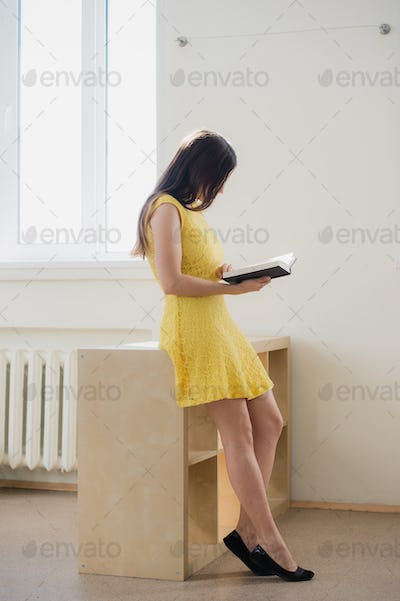 young woman reading a book at class or library