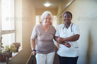 Nurse assisting a senior patient to walk