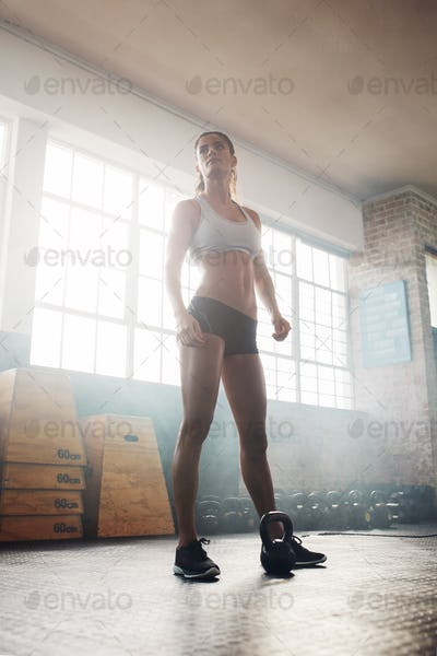 Fitness woman standing in crossfit gym