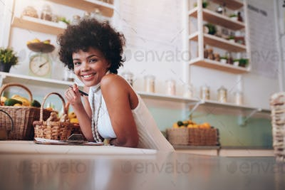 Smiling young woman working in a juice bar