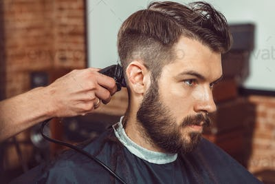 The hands of young barber making haircut to attractive man in barbershop