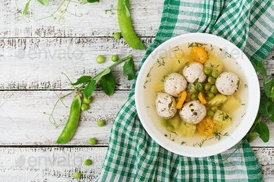 Dietary soup with chicken meatballs and green peas in a white bowl on a wooden background. Top view