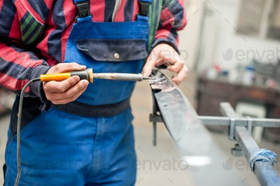 auto mechanic engineer welding plastic with special professional tool