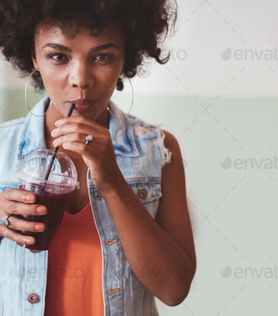 Attractive young woman drinking juice