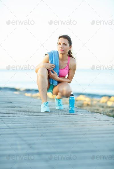 Sunny morning on the beach, athletic woman resting after running