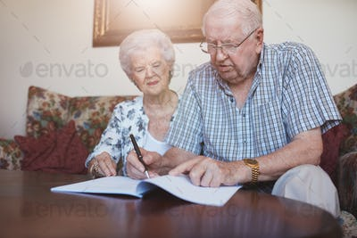 Senior couple at home signing paperwork together