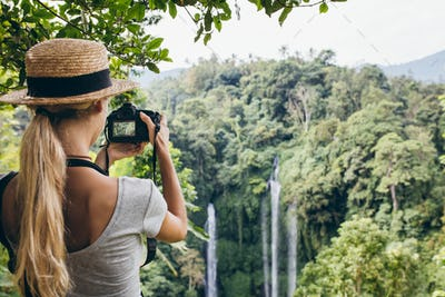 Female tourist photographing a waterfall in forest