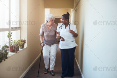 Senior woman with walking stick being helped by a female nurse a