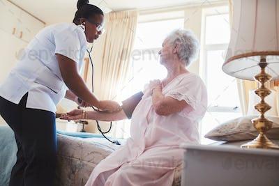 Female nurse checking blood pressure of a senior woman