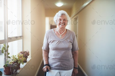 Happy senior woman with walking stick standing at home