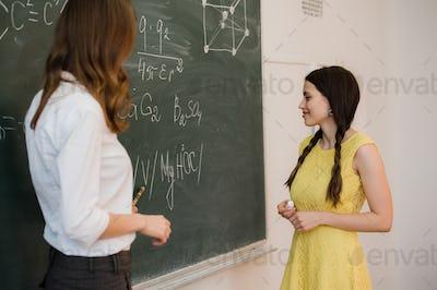 girl answers questions of teachers near a school board