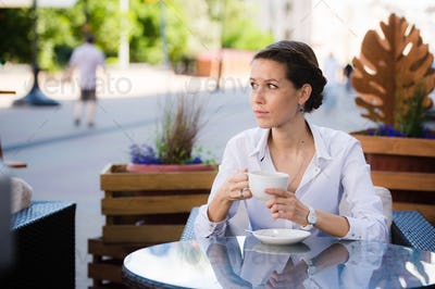 Elegant beautiful woman with notebook drinking coffee at cafe