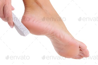 female scrubbing foot by pumice